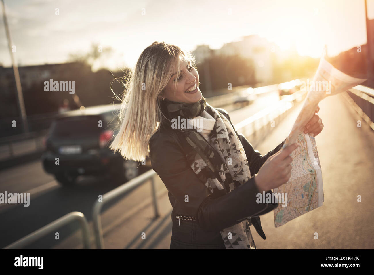 Tourist woman holding travelers map  to travel to destination - Stock Image