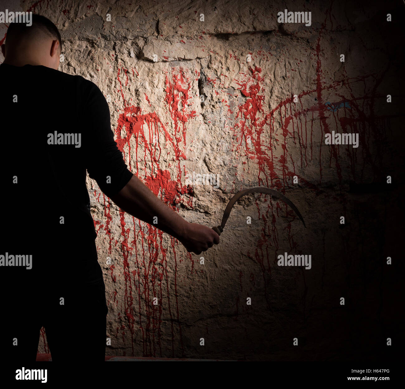 Shadowy figure holding sickle near blood stained wall for concept about murder and scary Halloween holiday Stock Photo