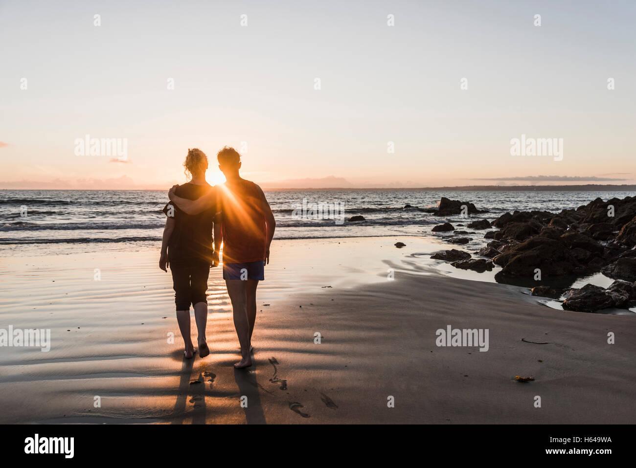 France, Corzon peninsula, couple walking on beach at sunset - Stock Image