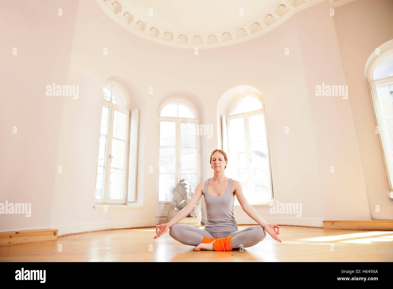 Woman in sunny yoga studio holding Lotus pose with closed eyes - Stock Image