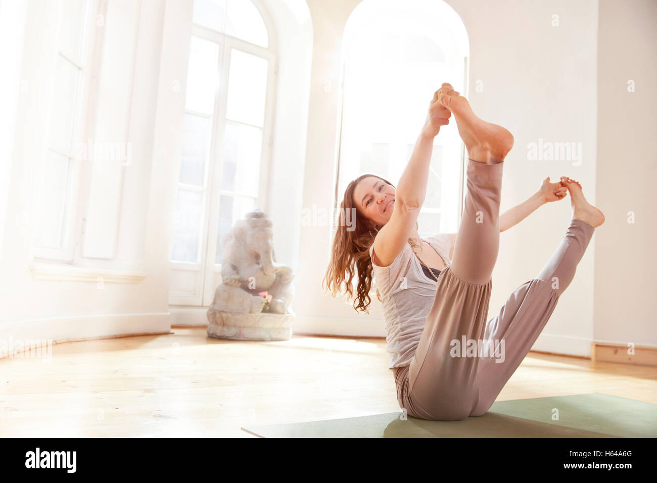 Woman in sunny yoga studio holding an extended Navasana pose - Stock Image