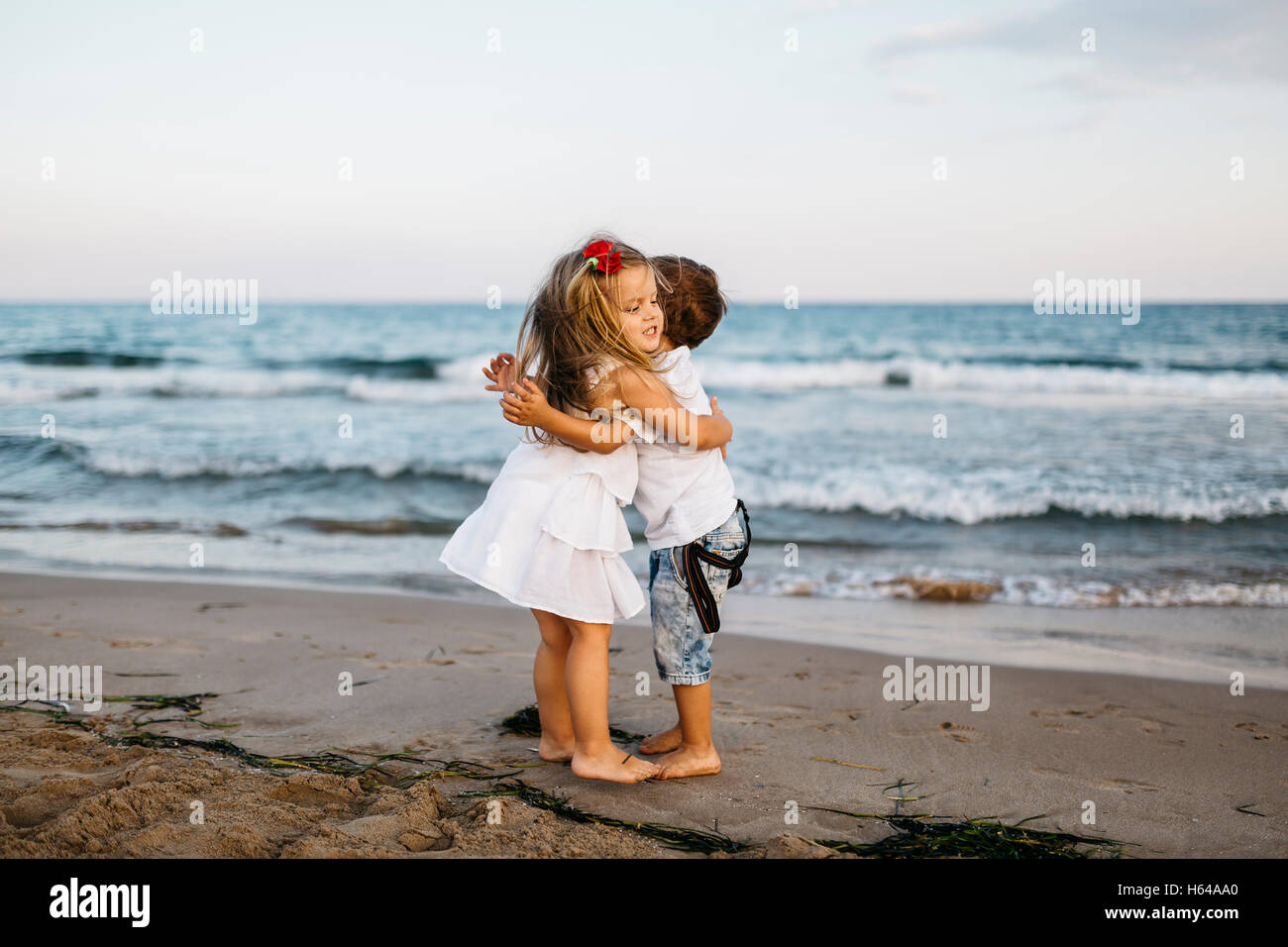 little girl hugging little boy on the beach stock photo 124256440