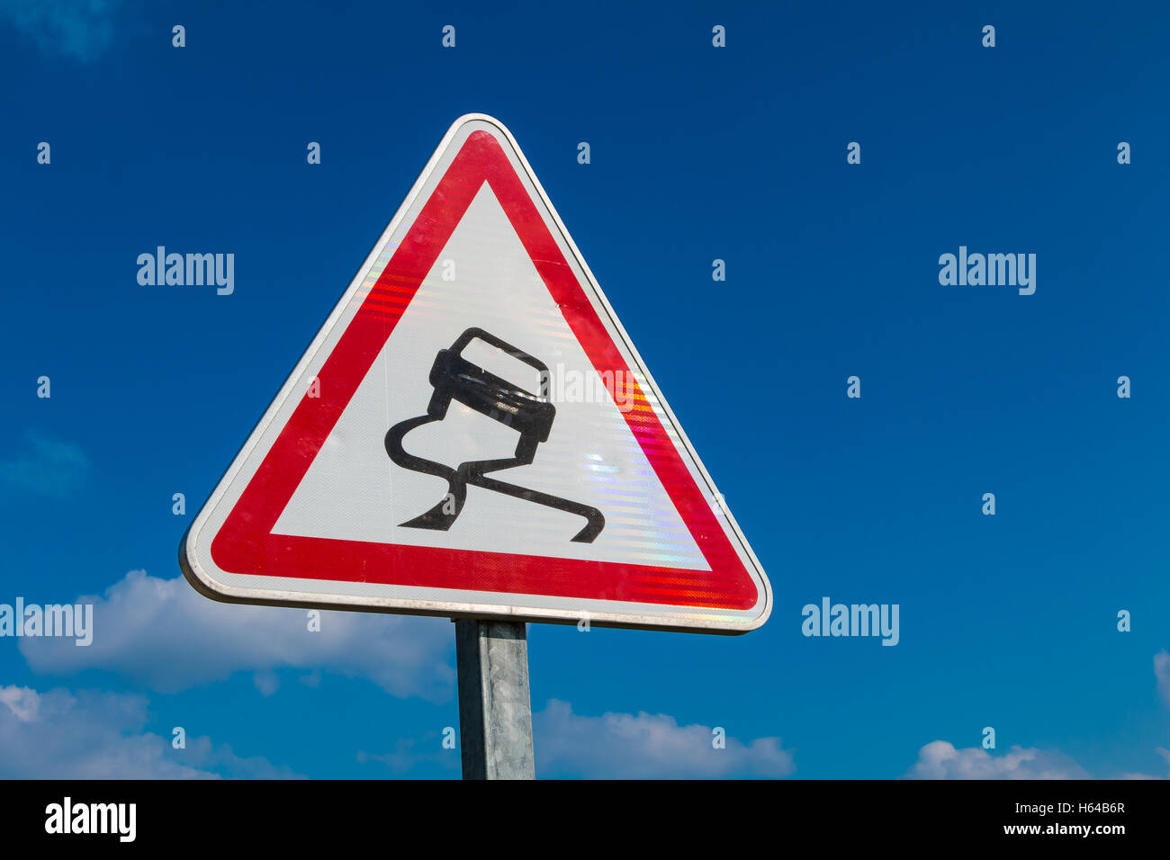 Slippery Road Warning Sign on blue sky - Stock Image