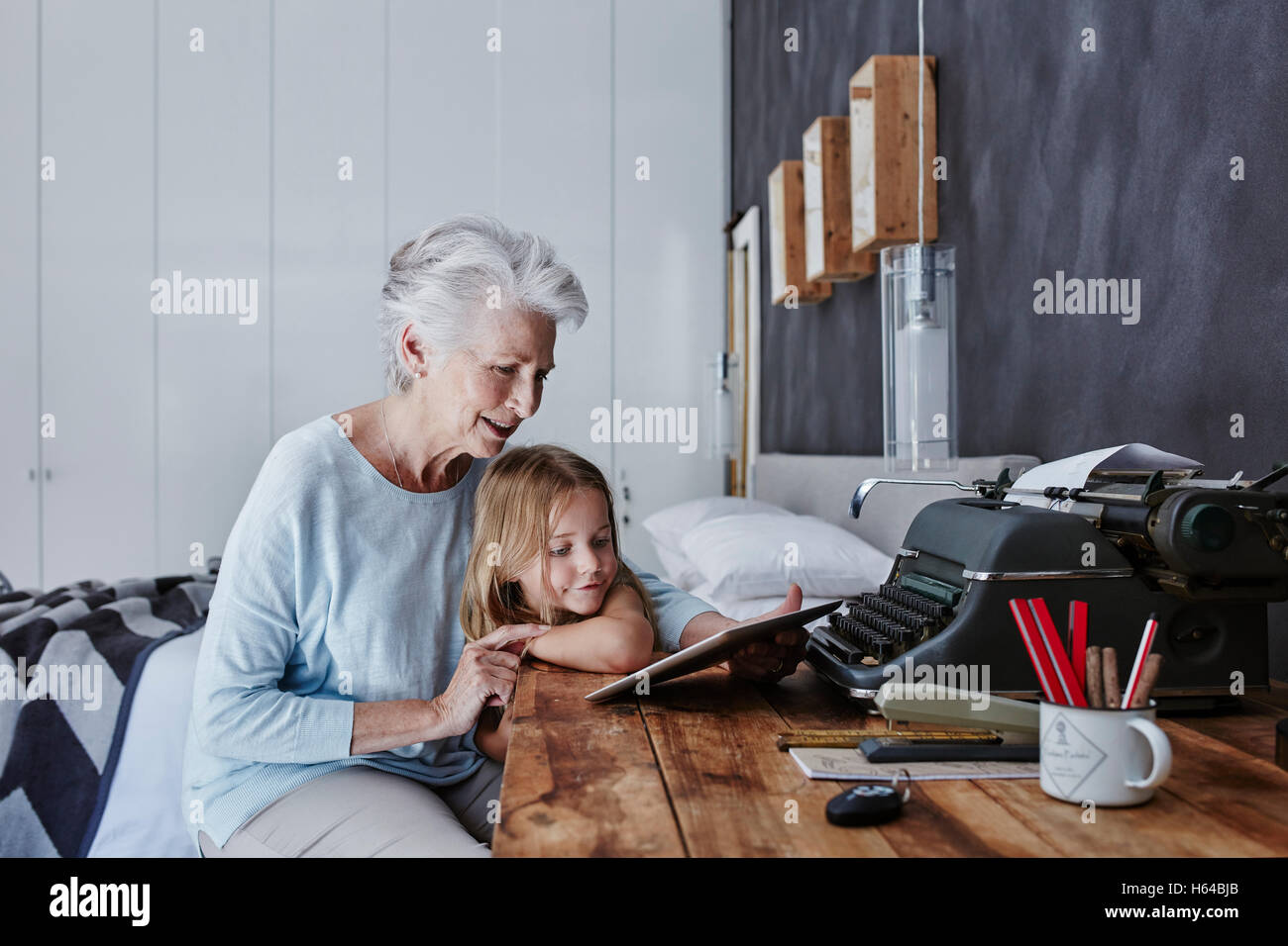 Grandmother and granddaughter looking at tablet at home Stock Photo