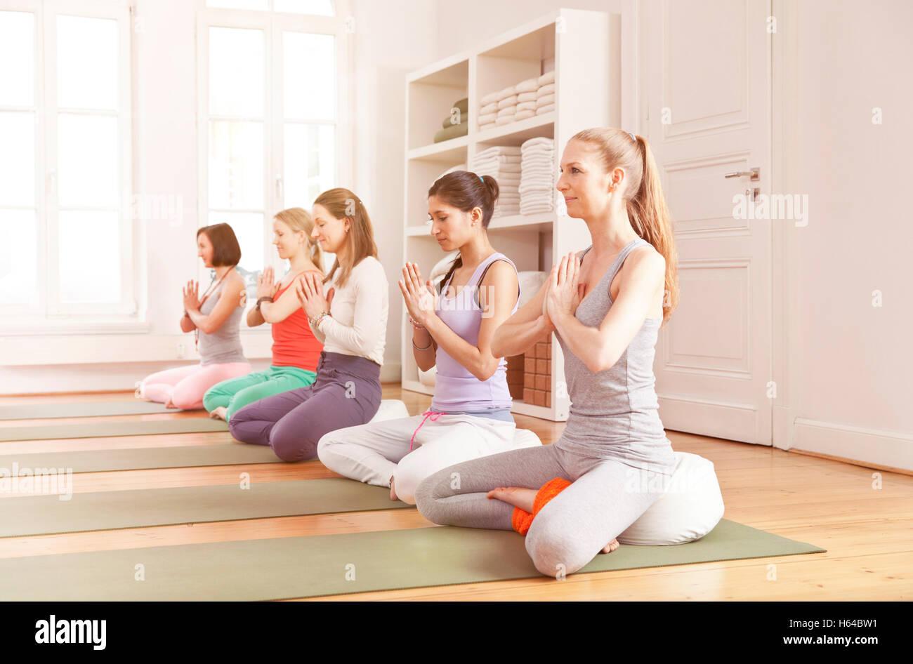 Group of women in yoga studio sitting in Lotus pose - Stock Image