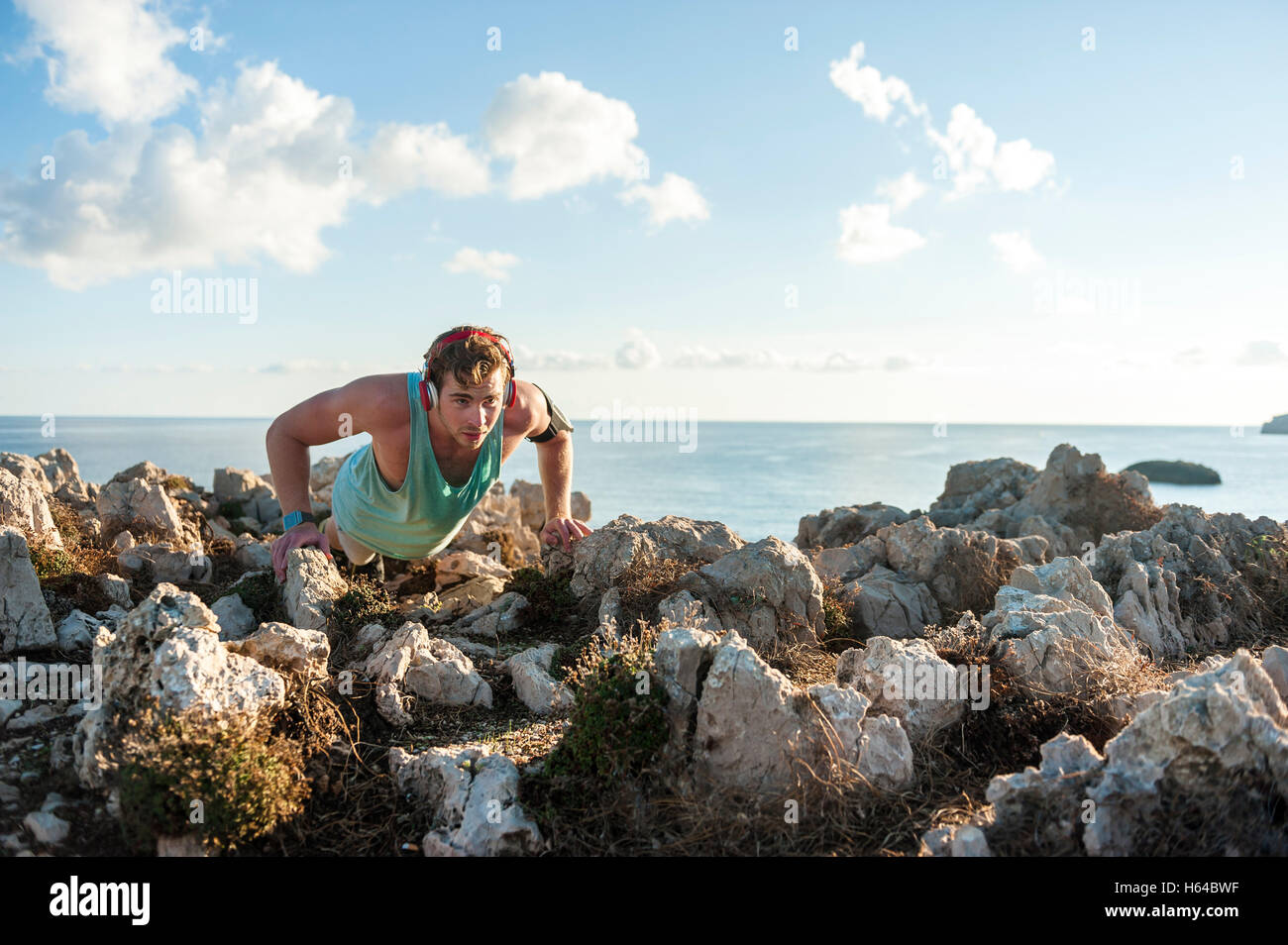 Spain, Mallorca, Sportsman standing on rocky coast in the morning, pushup - Stock Image