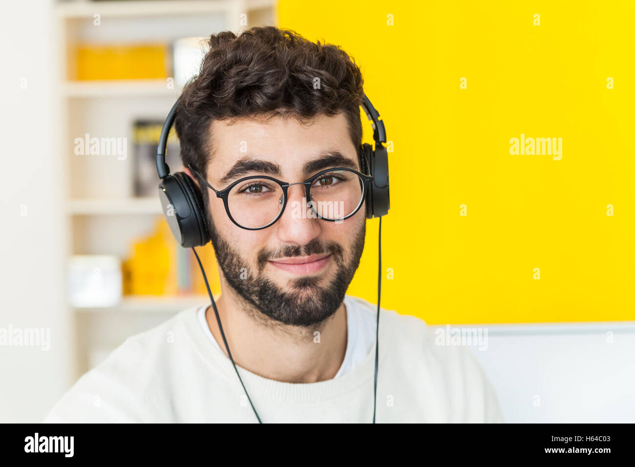 Portrait of smiling man with glasses and headphones - Stock Image