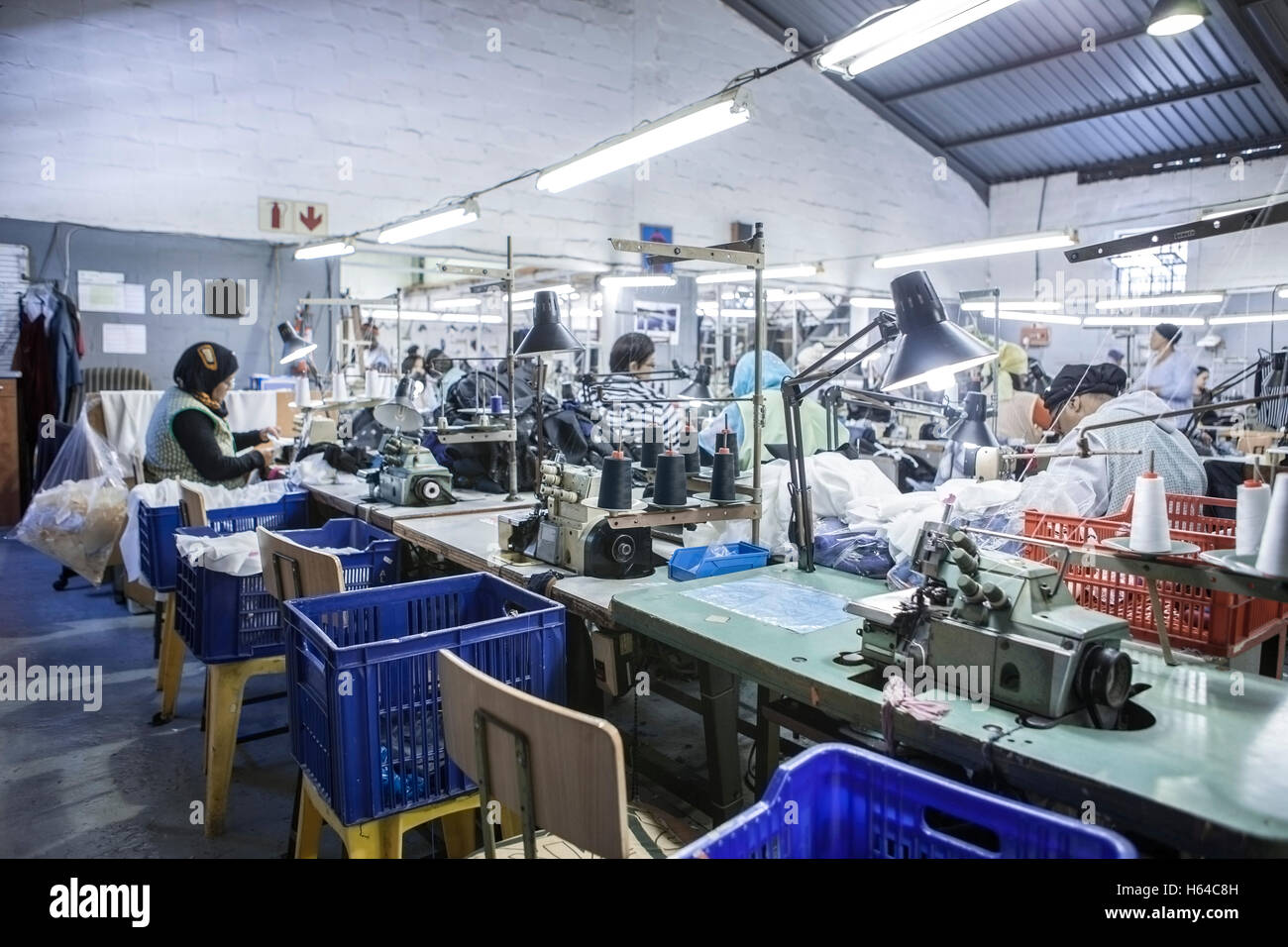 Seamstresses in factory sewing clothes - Stock Image