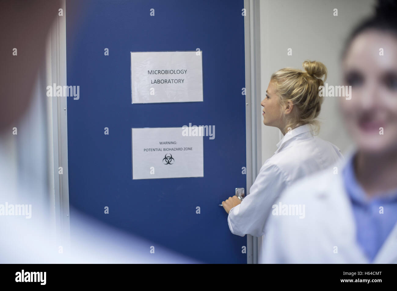 Woman in lab coat opening door to microbiology laboratory - Stock Image