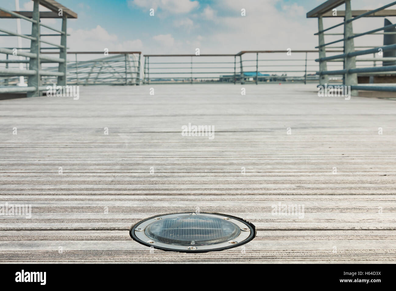 Solar Round Deck light LED on a wooden bridge with blue sky - Stock Image