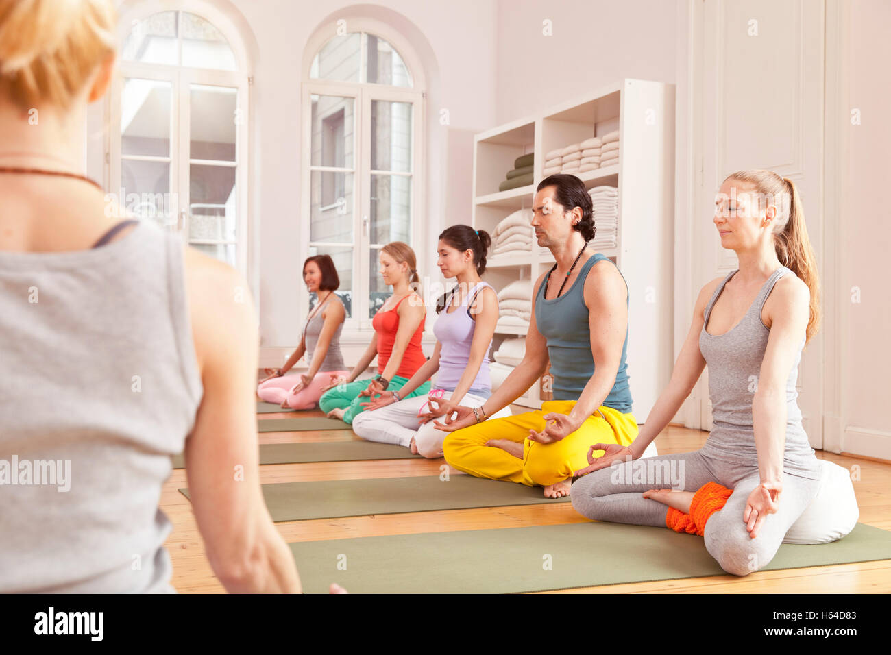 Group of people in yoga studio sitting in Lotus pose next to instructor - Stock Image