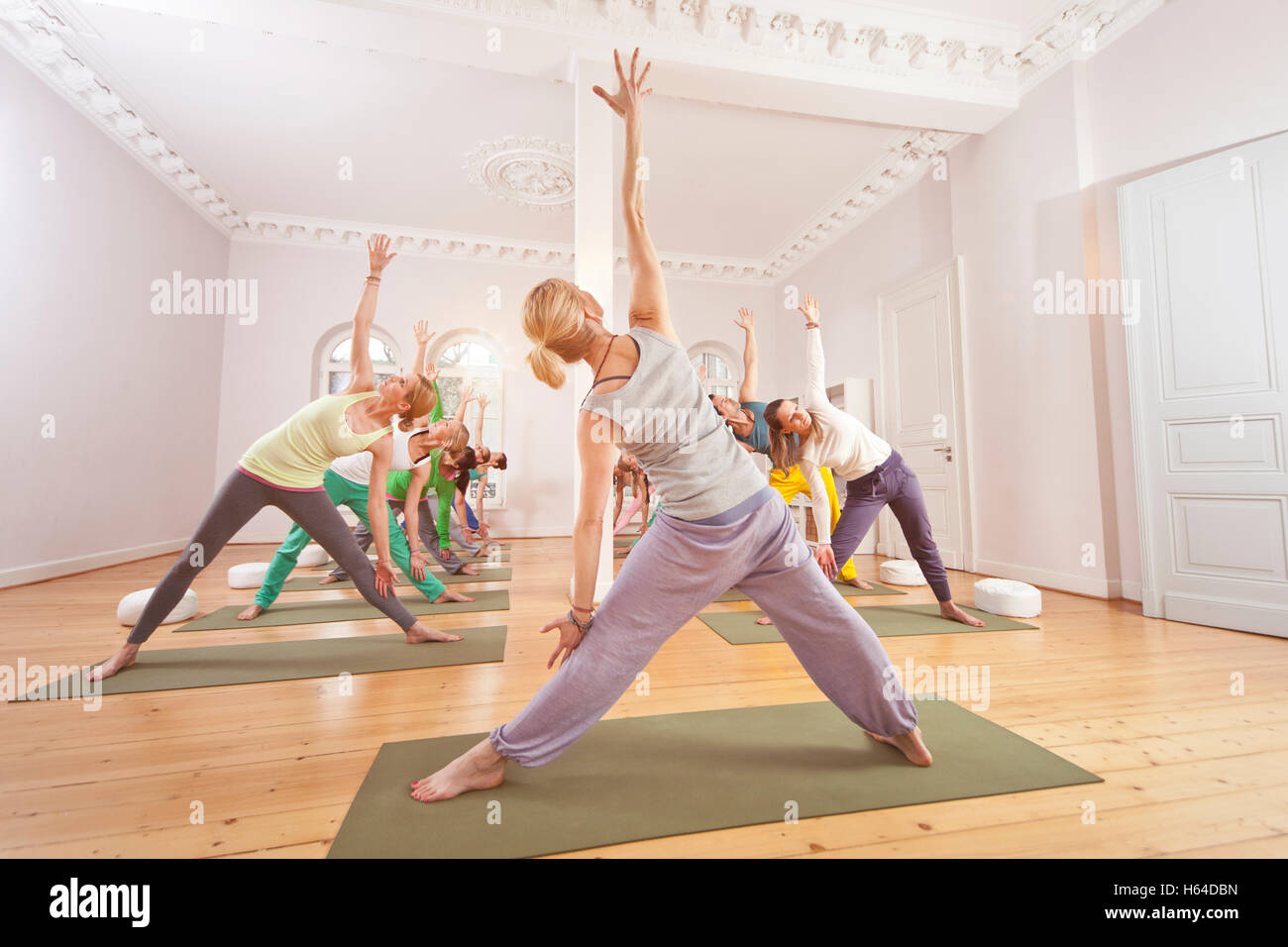 Group of people in yoga studio holding the extended triangle pose - Stock Image