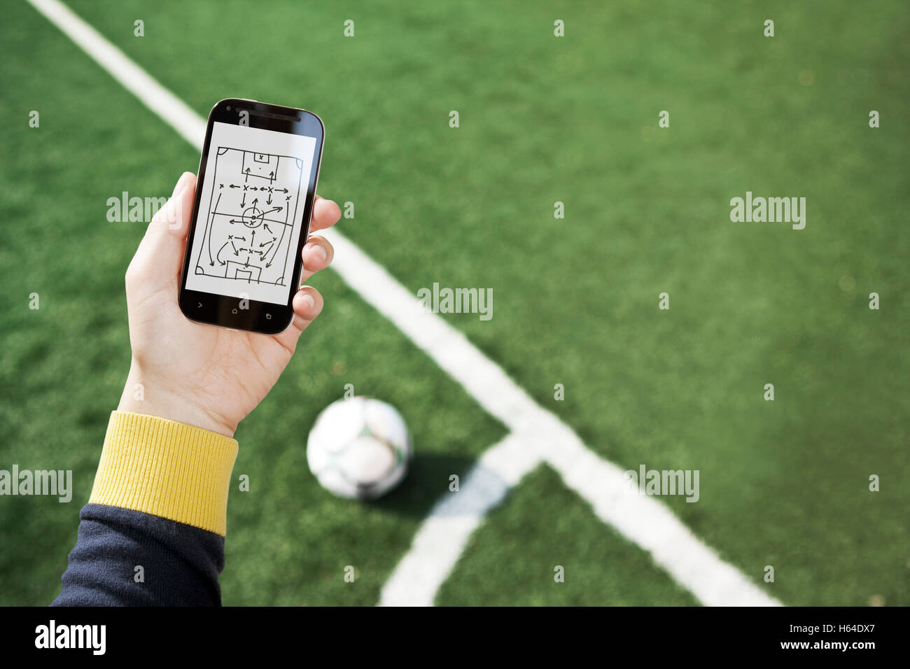 Hand holding smart phone with match tactics over soccer field - Stock Image