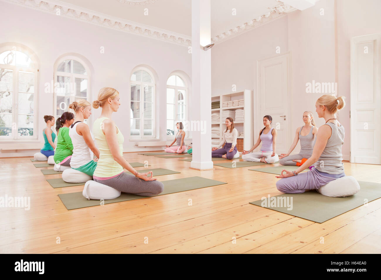 Group of women in yoga studio sitting in Lotus pose with instructor - Stock Image