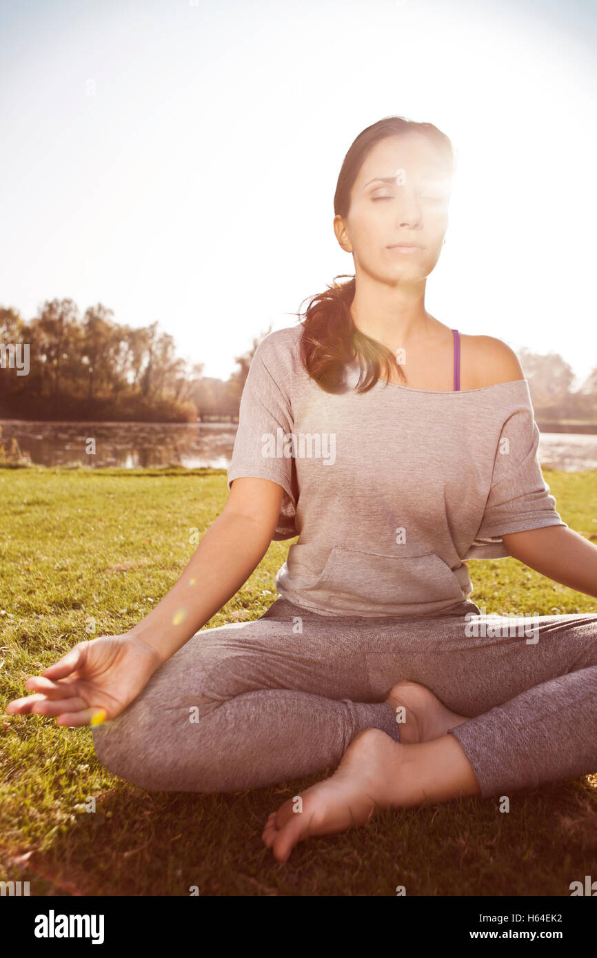 Woman with closed eyes relaxing in Lotus yoga pose - Stock Image