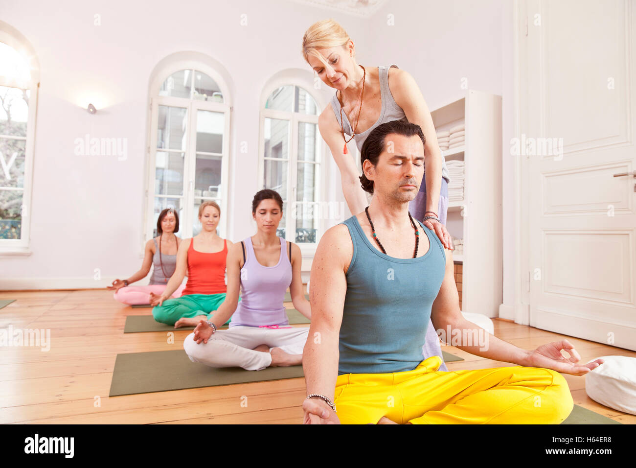 Group of people in yoga studio sitting in Lotus pose while instructor straightens their backs - Stock Image