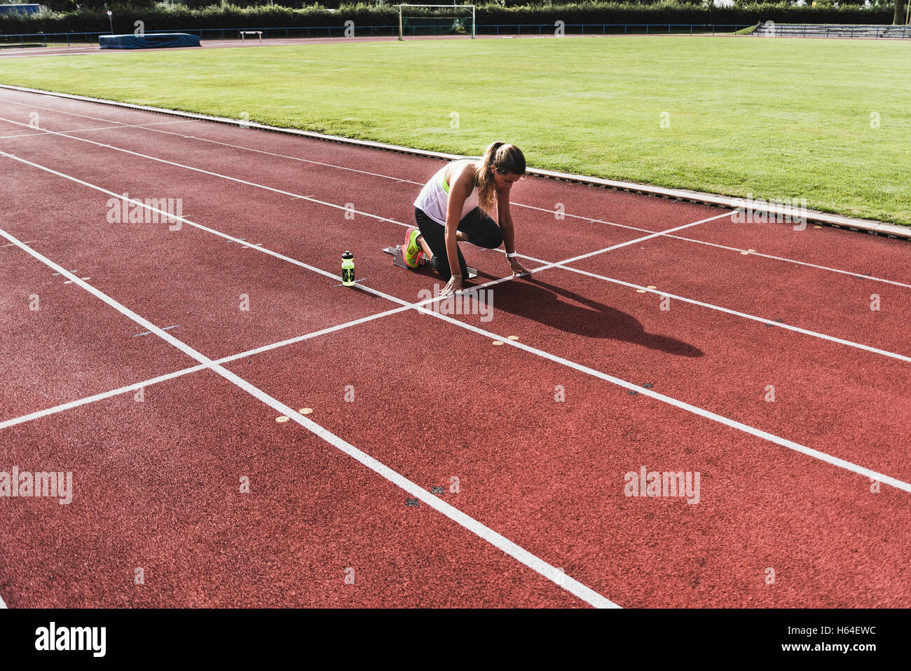 Young woman on tartan track in starting position Stock Photo