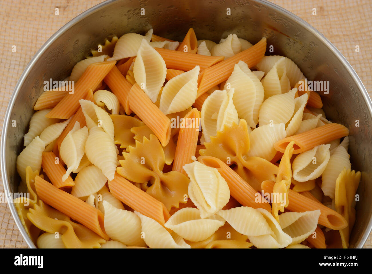Variety of cooked pasta in stainless steel bowl - Stock Image