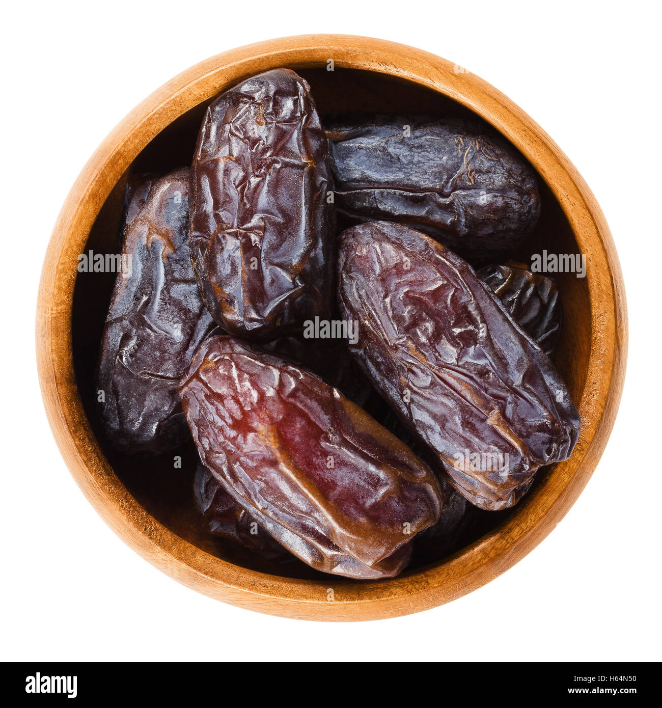 Dried Medjool dates from Morocco in a wooden bowl on white background, also called Mejhool. Large, sweet and succulent - Stock Image