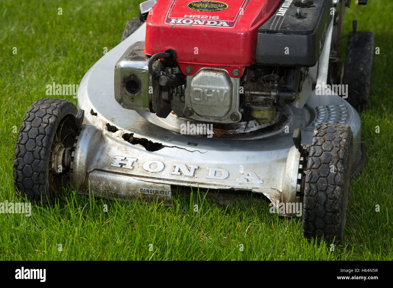 Lawnmower damaged by stones thrown up by the rotor - Stock Image