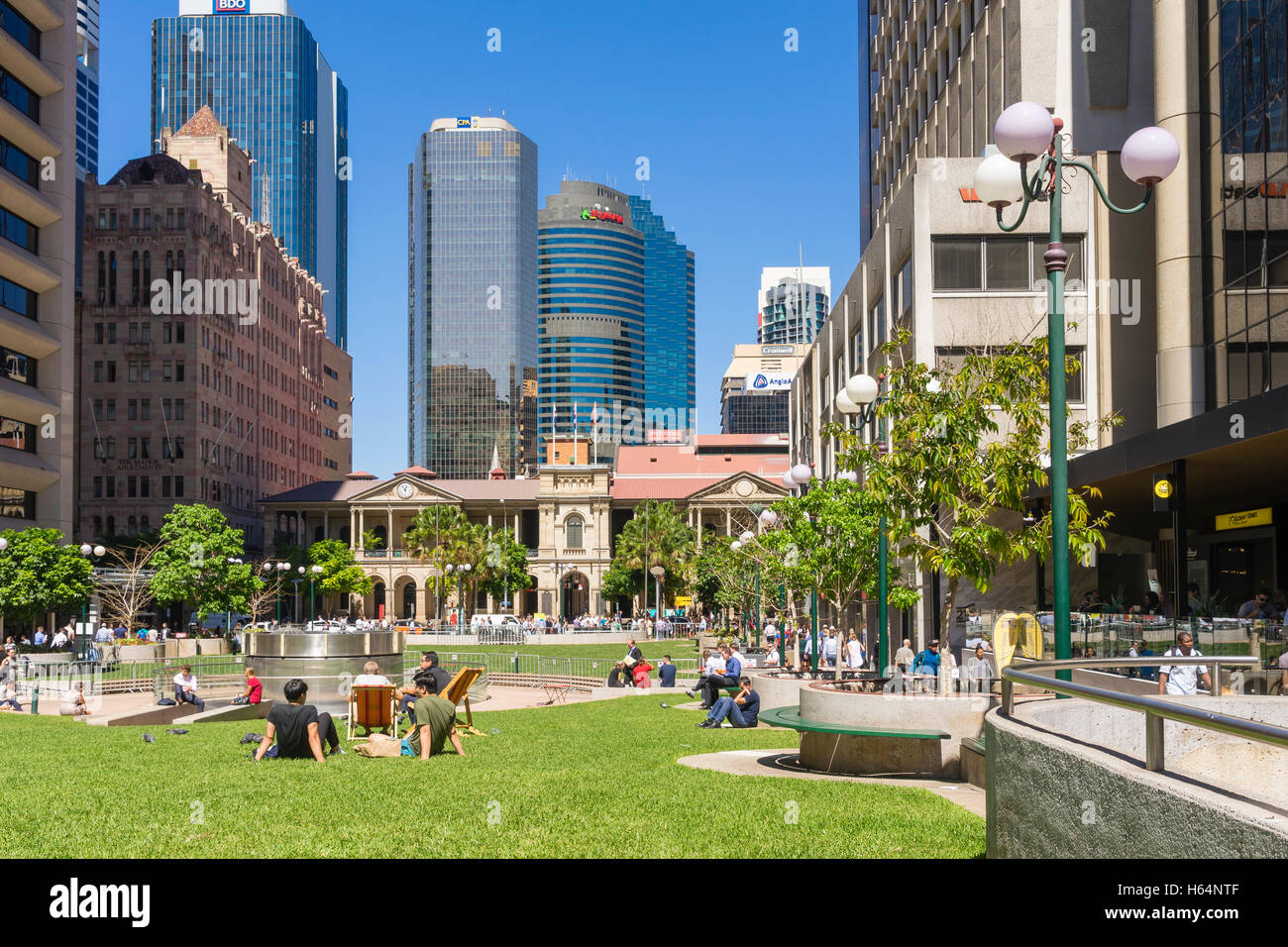 People sitting in the lawn and Brisbane skyline - Stock Image
