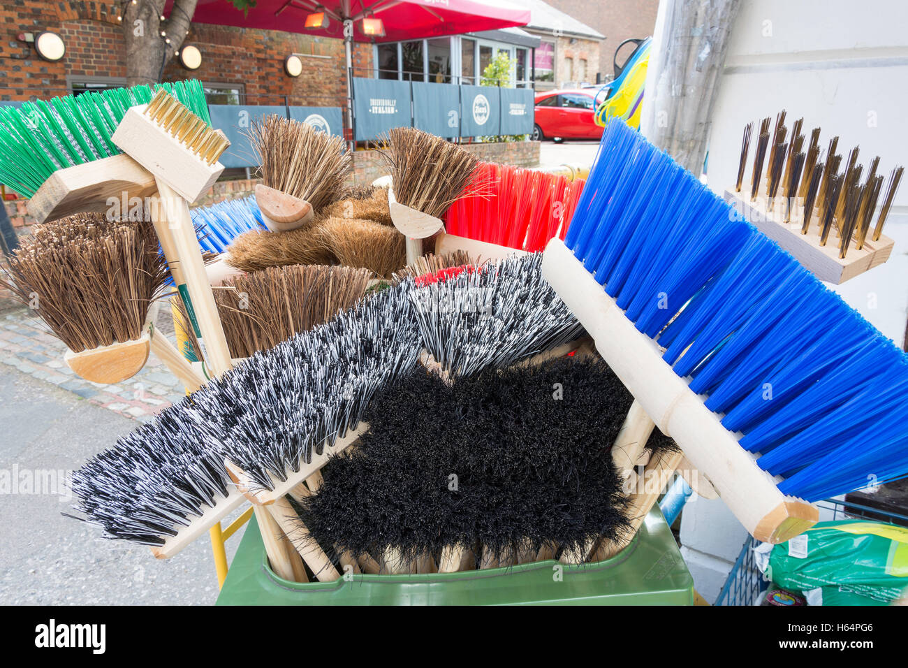Selection of brooms outside hardware shop, London Road, Sevenoaks, Kent, England, United Kingdom - Stock Image