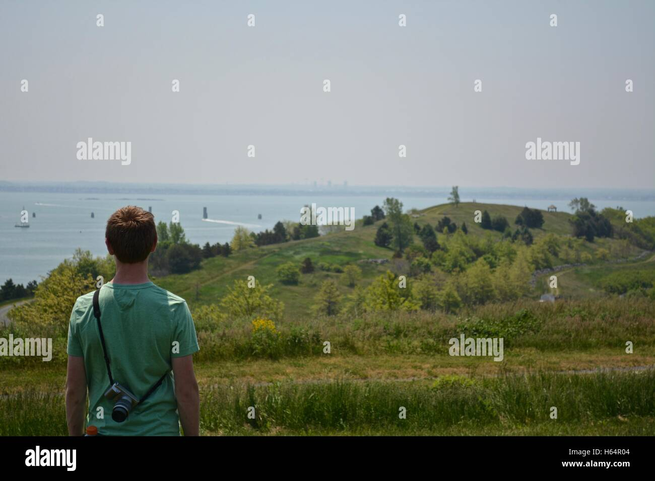 A young person on a hill atop an island in Boston Harbor. - Stock Image