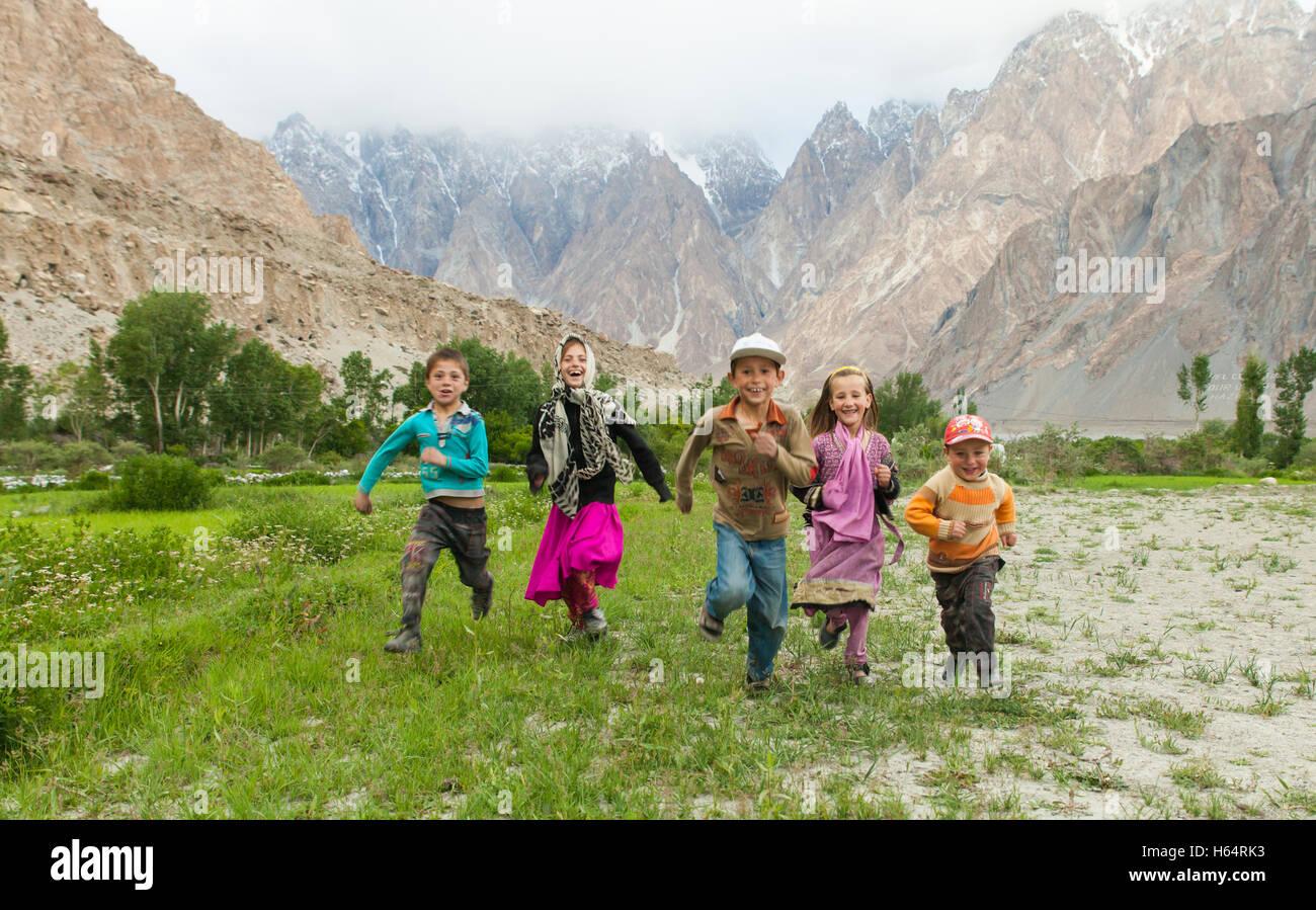 children running together in stunning scenery of Karakoram mountains in Passu, northern Pakistan - Stock Image