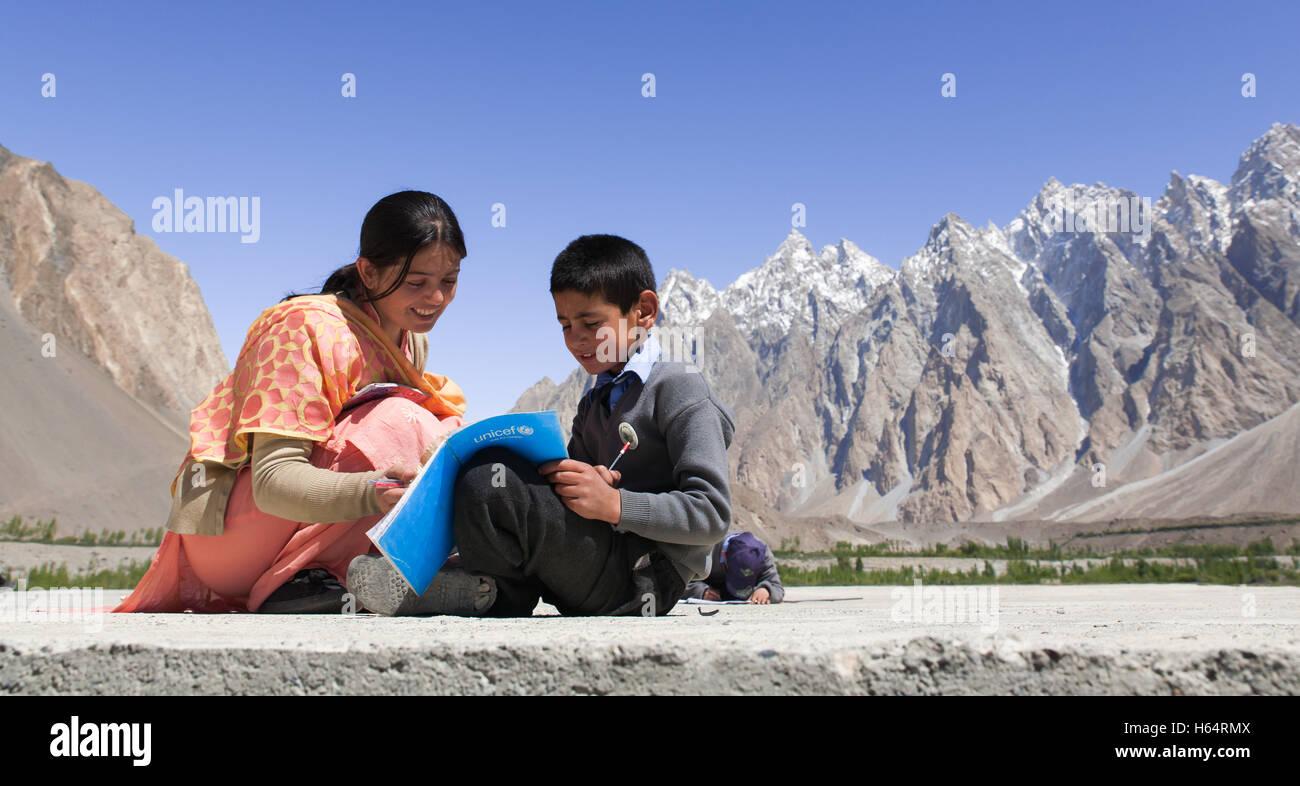 teacher helping student study on rooftop of school located in Karakoram mountains in Passu, northern Pakistan - Stock Image