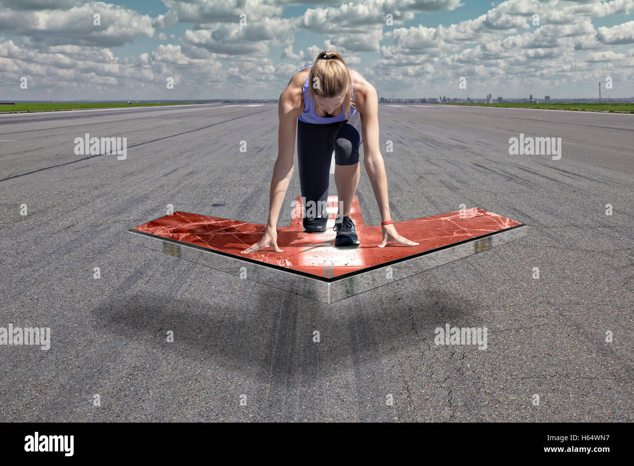 Female runner kneels in start position on a red floating arrow platform, which is placed above an airport runway Stock Photo