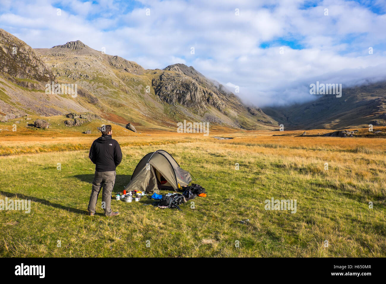 Wild camping in the Upper Esk valley in the Lake District, a young man stands by his tent - Stock Image