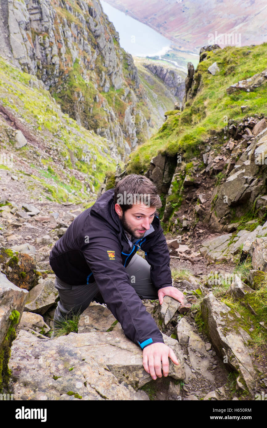 Male in his mid-twenties scrambling in Lord's Rake on Scafell,the Lake District, whilst wearing a Paramo jacket - Stock Image