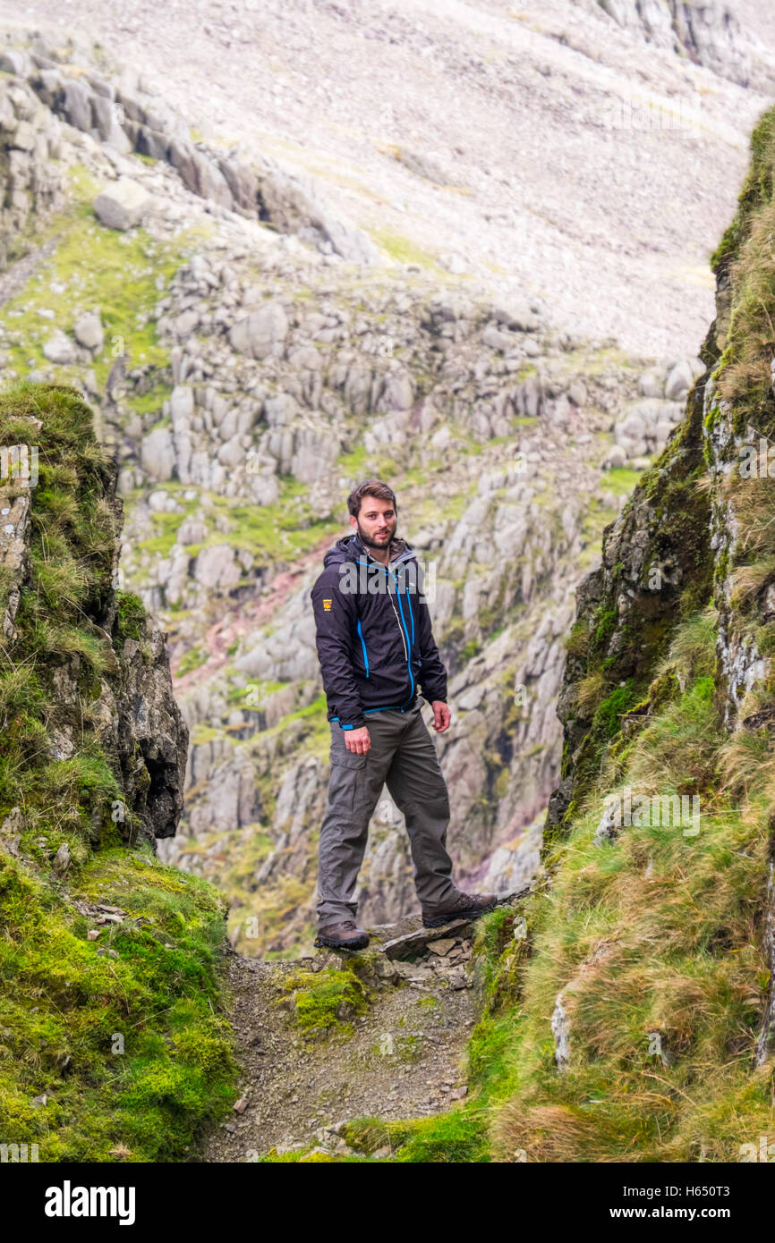 Male in his mid-twenties hill-walking in the Lake District, wearing a Paramo jacket. On Lord's Rake, Scafell - Stock Image