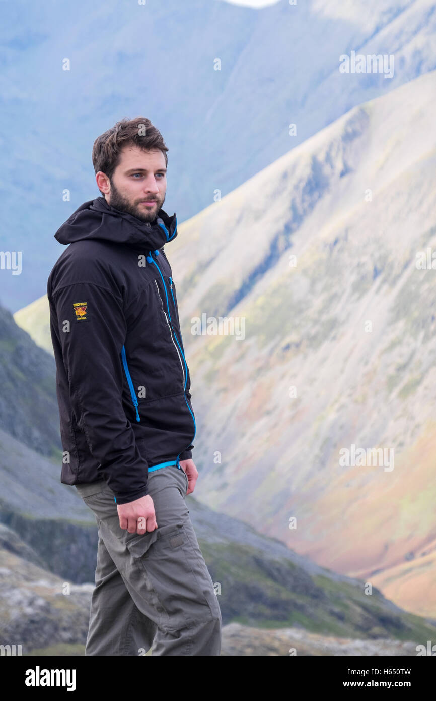 Male in his mid-twenties hill-walking in the Lake District, wearing a Paramo jacket - Stock Image