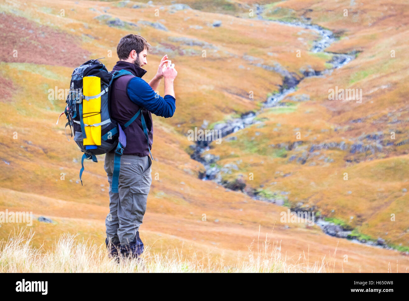 Male in his mid-twenties hill-walking in the Lake District, taking a photo with a smart phone - Stock Image
