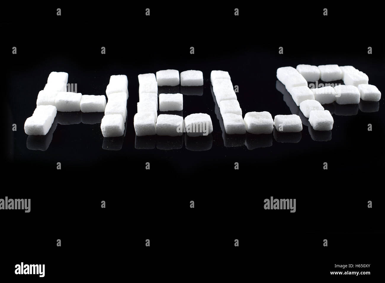 Sugar cubes forming word help. - Stock Image