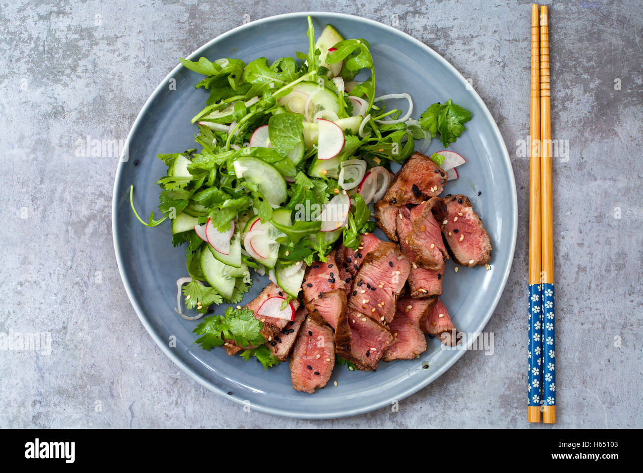 Asian beef salad with cucumber and herb salad and black and white sesame seeds - Stock Image