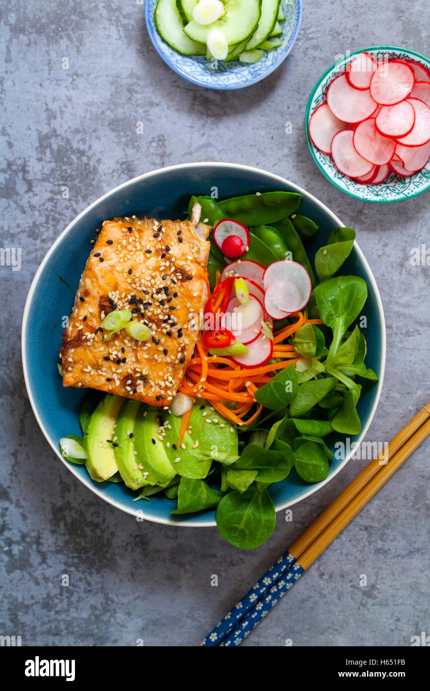 Salmon teriyaki with pickled carrots and radishes, lamb lettuce and avocado - Stock Image