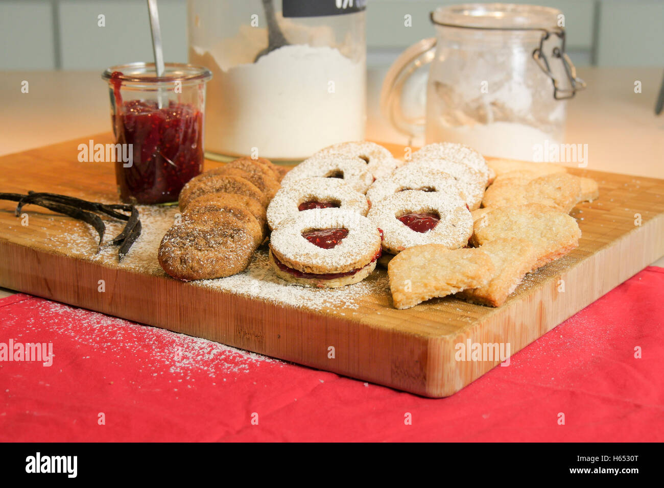 Christmas cookies on a wooden board with jam and a jar of baking powder. - Stock Image