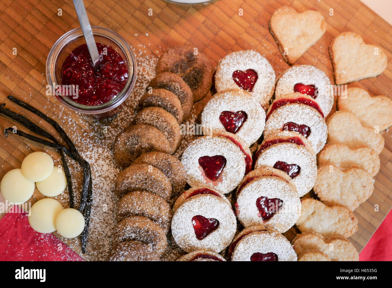 cookies and biscuits presented on a wooden board with ingredients next to it - Stock Image