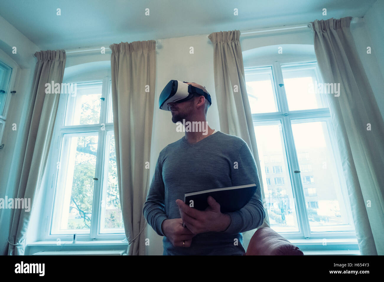 Real Estate agent in home wearing Virtual Reality (VR) goggles - Stock Image