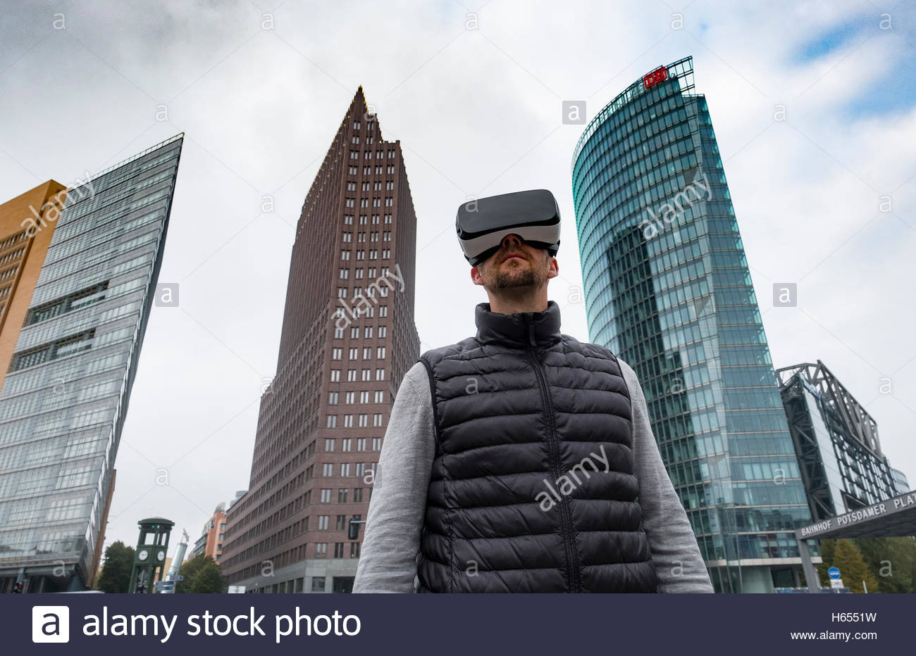 Man wearing Virtual Reality (VR) goggles at Potsdamer Platz in Berlin, Germany - Stock Image