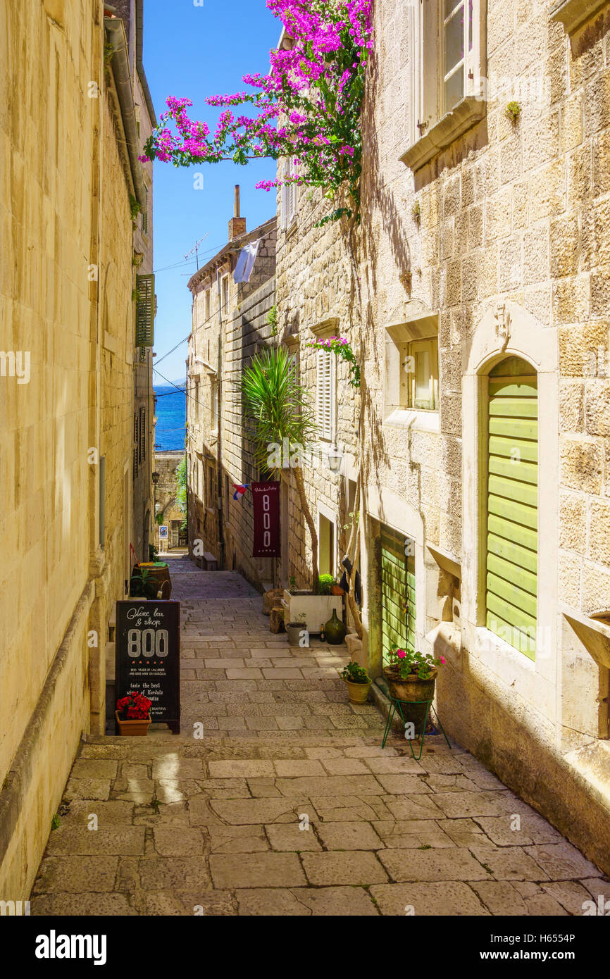 KORCULA, CROATIA - JUNE 25, 2015: An alley in the old city of Korcula, with local businesses, in Dalmatia, Croatia - Stock Image