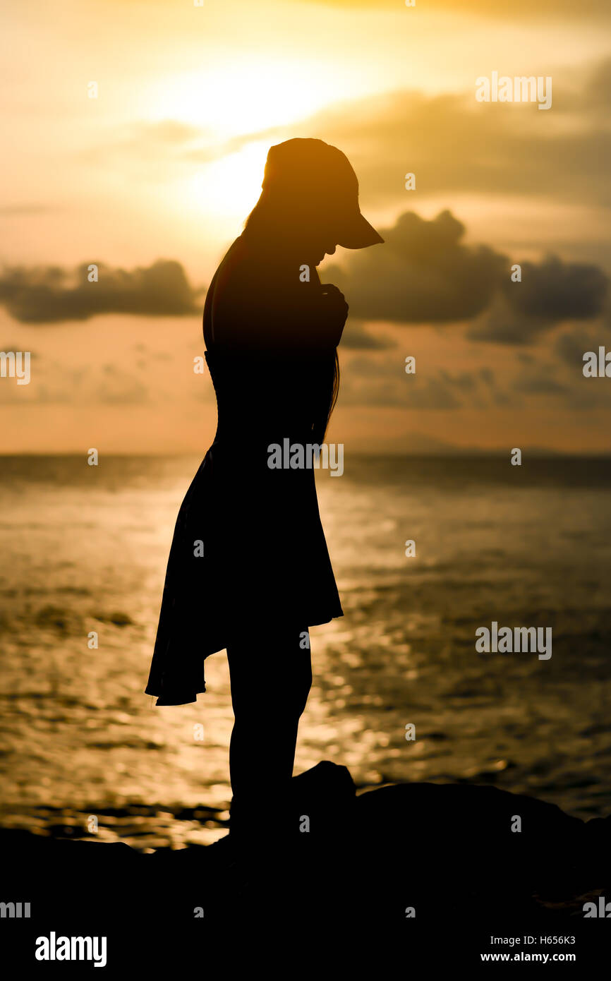 woman standing wear a cap with sunset silhouette Stock Photo