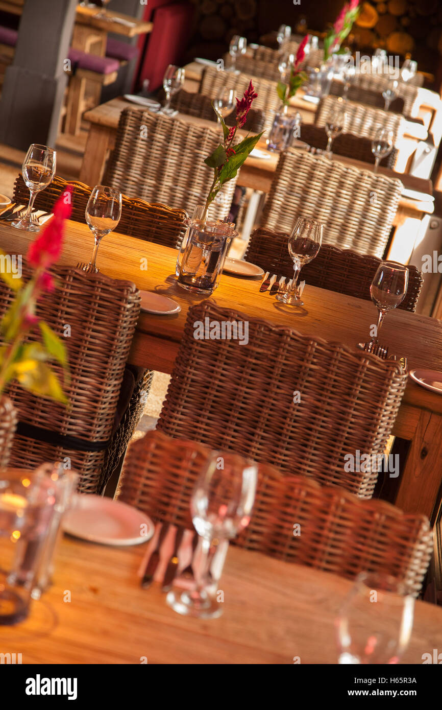A row of wooden tables with wicker chairs laid for lunch in a restaursant, wine glasses, cutlery, flowers - Stock Image