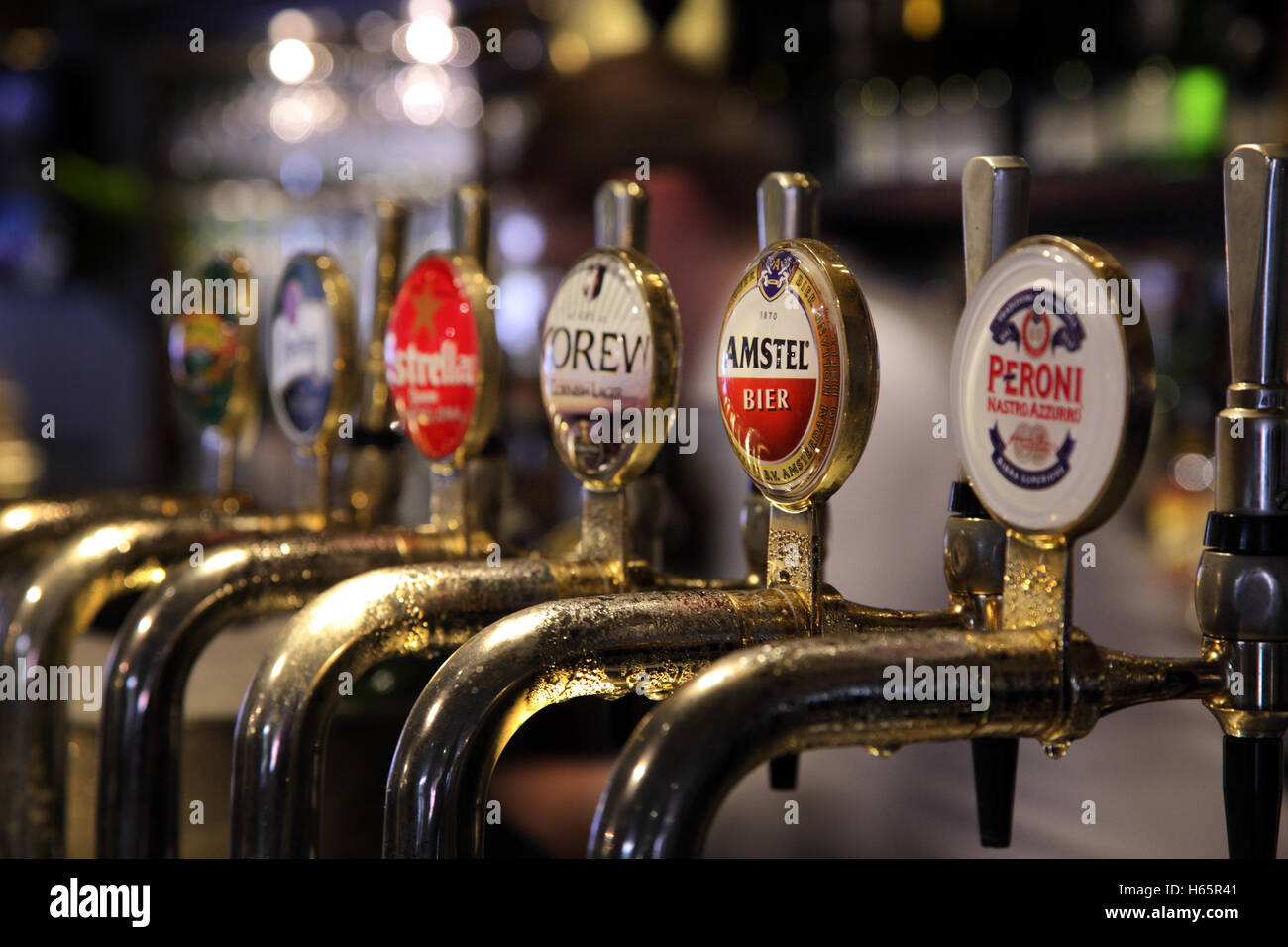 Row of lager and beer taps on a pub bar, Peroni, Amstel, Korev, Estrella Damm, - Stock Image
