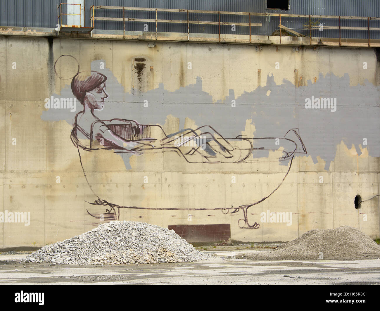 Uncommon graffiti: line drawing of man in bath tub on the wall of industrial building - Stock Image