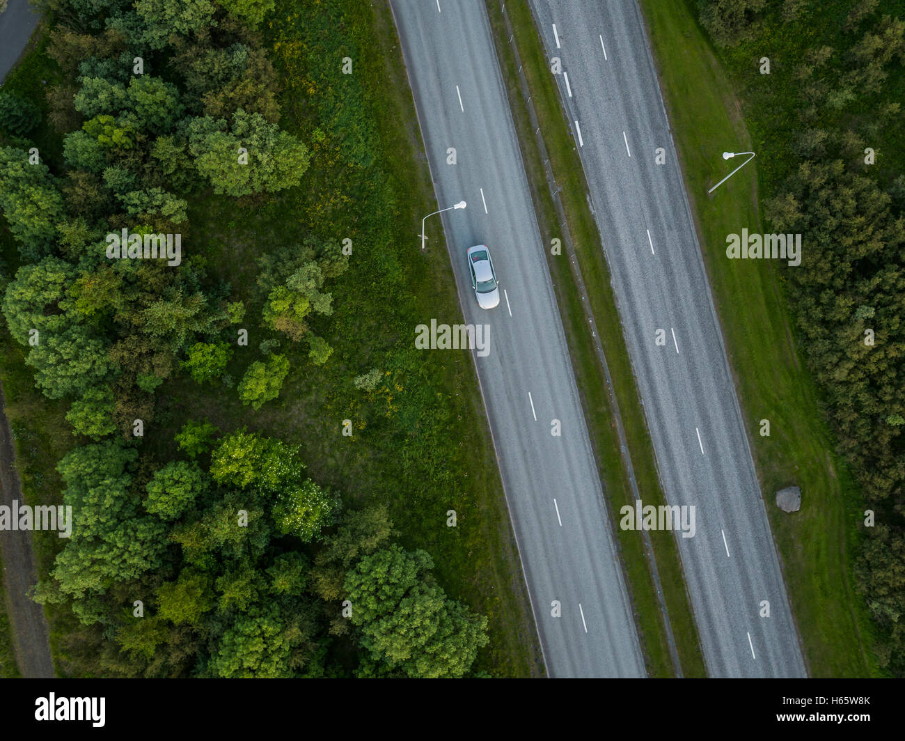 Top view of single car driving alone on the road, Reykjavik, Iceland.  This image is shot using a drone. - Stock Image