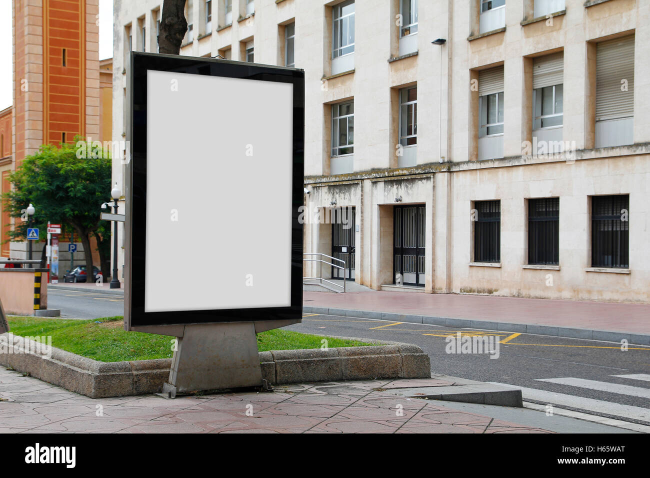 Blank billboard mock up in the street, in front of a building Stock Photo
