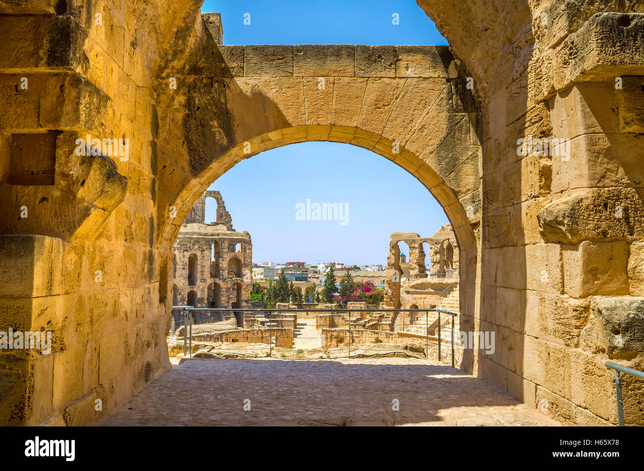 The view on the roman ruins of amphitheatre through the arch of its hall, El Jem, Tunisia. - Stock Image